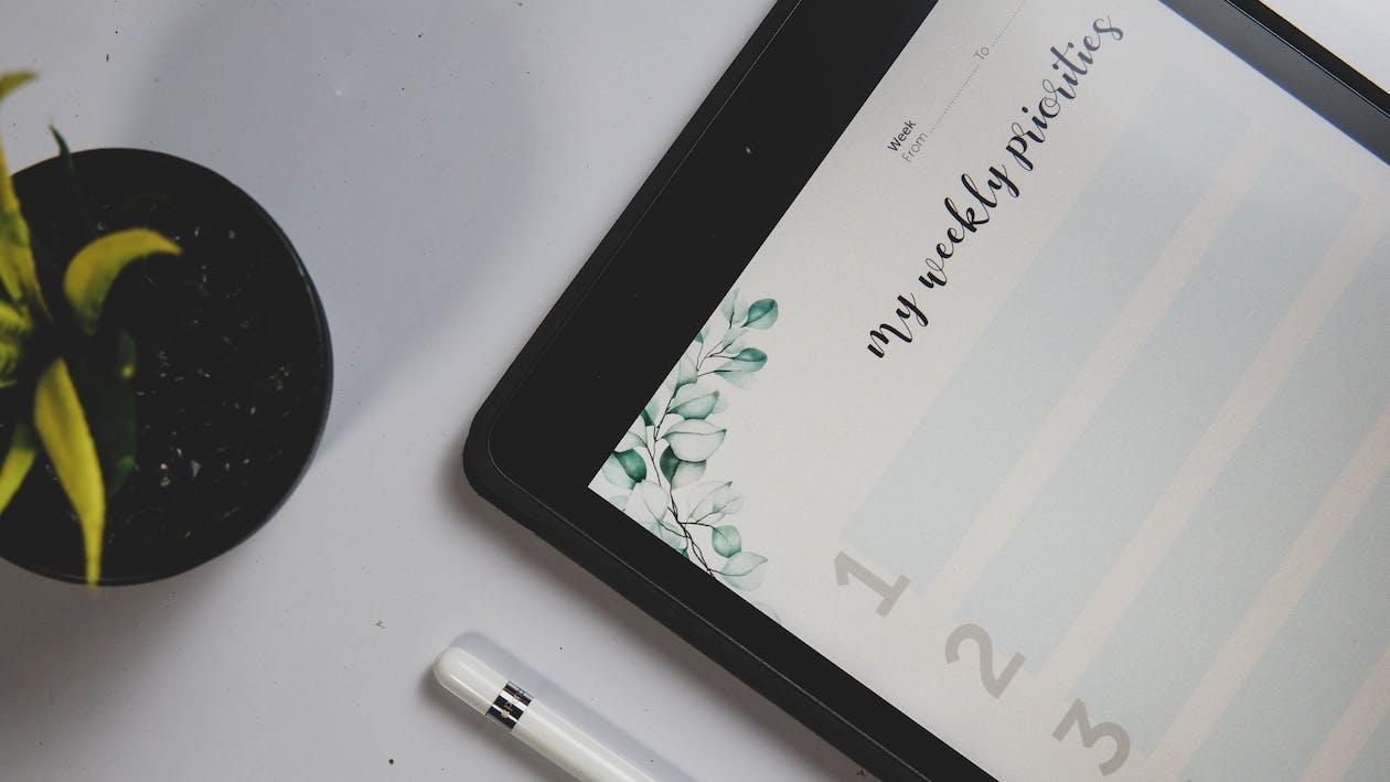 White Pen Beside Black Tablet Computer