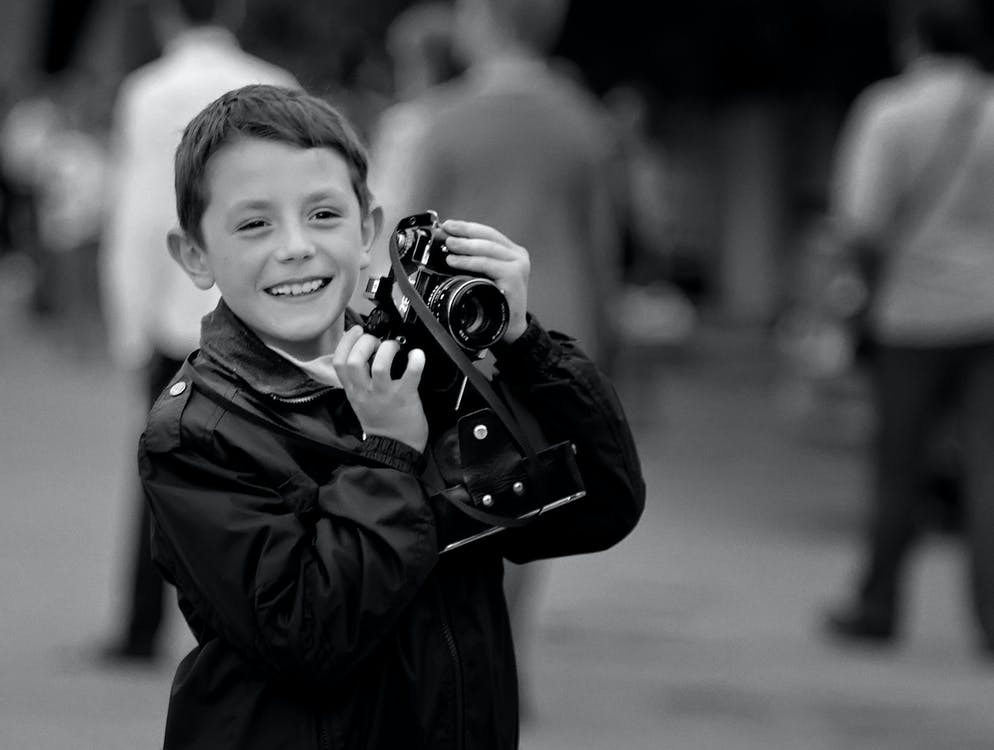Grayscale Photo of Boy Holding Camera