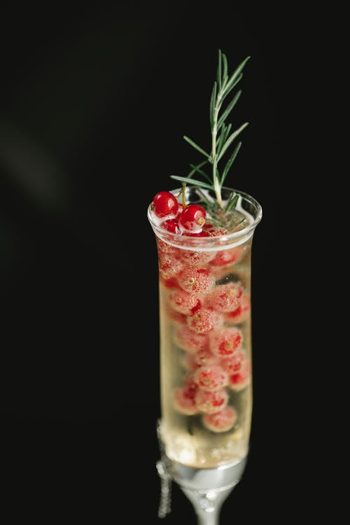 Crystal flute glass filled with alcoholic drink and fresh red berries on black background