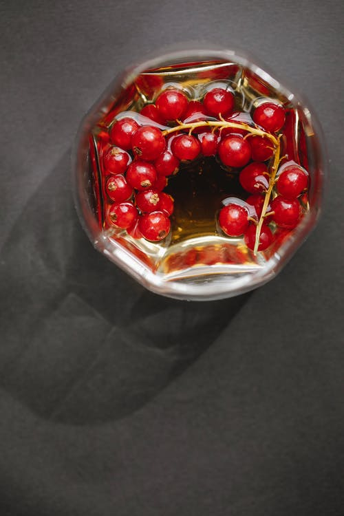 Glass with red berries on table