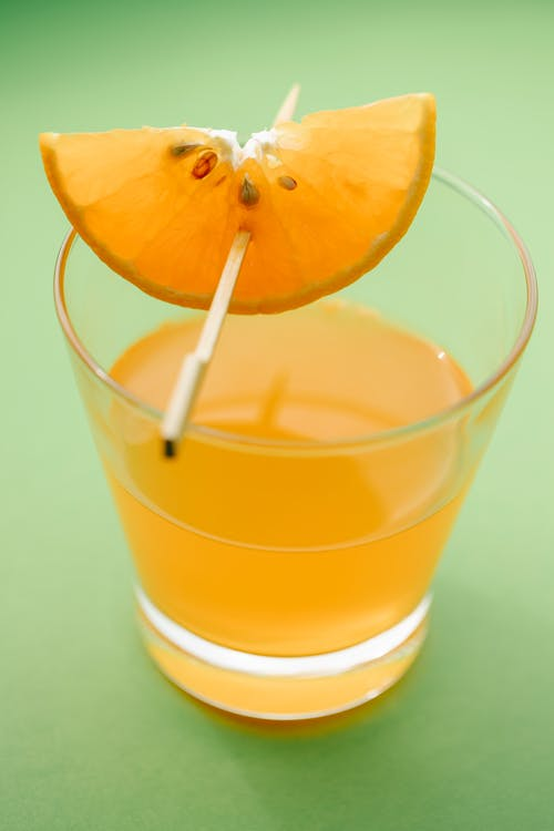 Crystal glass with orange juice decorated with slice of fresh ripe citrus fruit