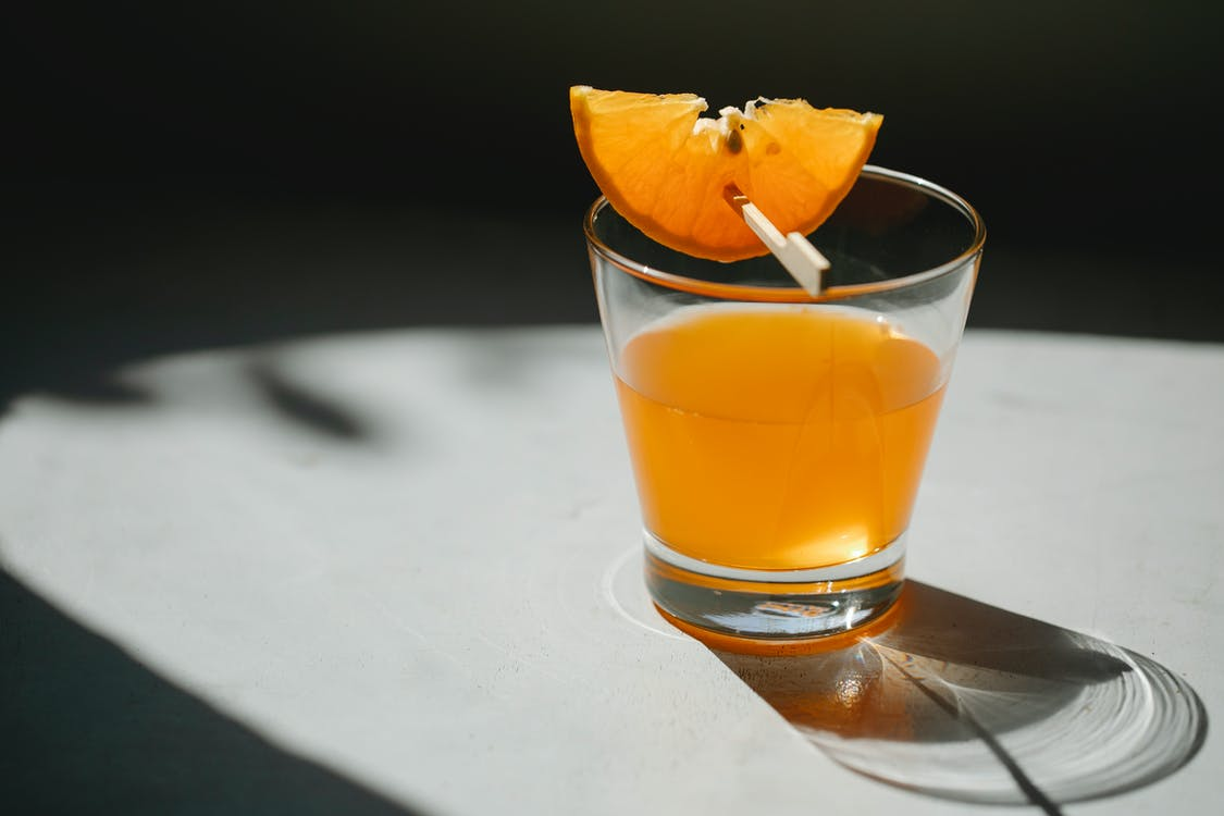 Glass of alcohol drink decorated with slice of orange on wooden stick placed on white table on blurred black background