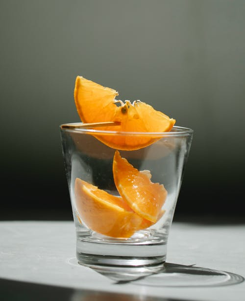 Glass with slices of orange on table
