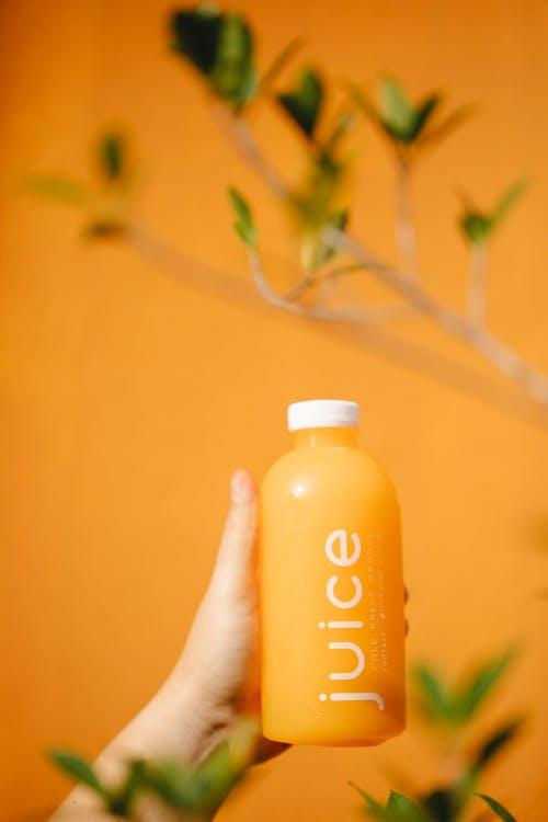 Crop person with bottle of orange juice