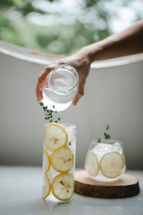 Unrecognizable person pouring water from jug into glass with lemon slices placed on table near drink with ice cubes in room with round window on blurred background