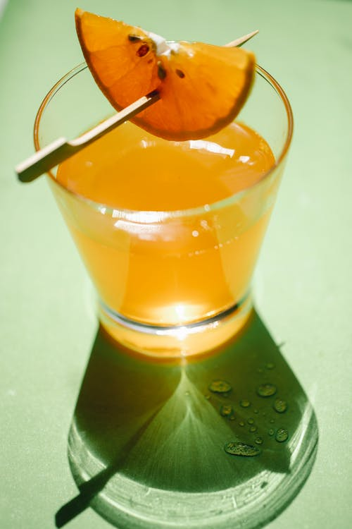 Glass of orange drink on surface