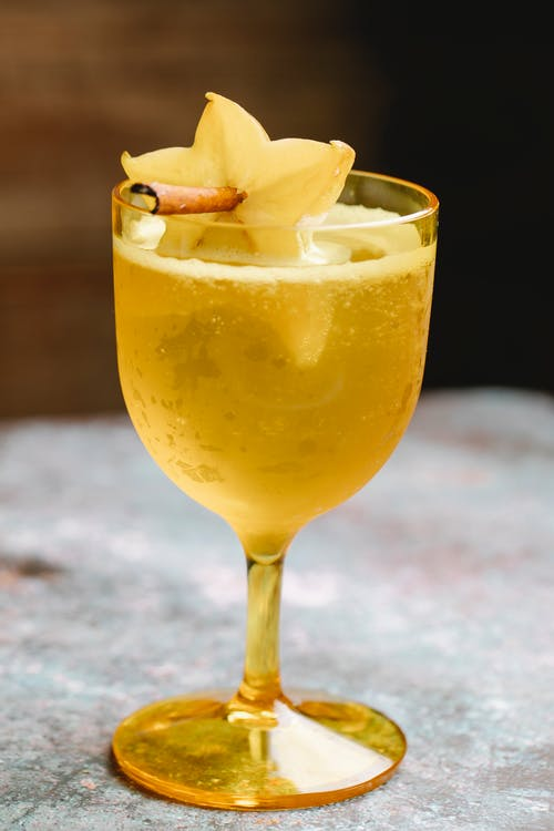 Wineglass filled with fizzy beverage decorated with carambola fruit on cinnamon stick placed on marble table on blurred background in kitchen