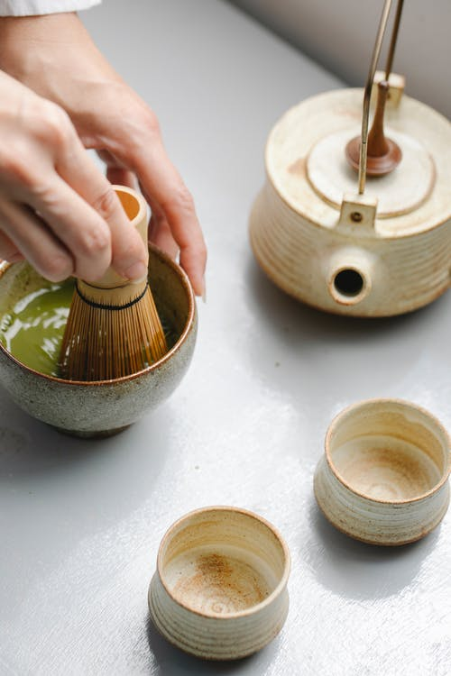 From above of crop person mixing matcha powder in bowl with bamboo whisk while brewing healthy tea on table with teapot