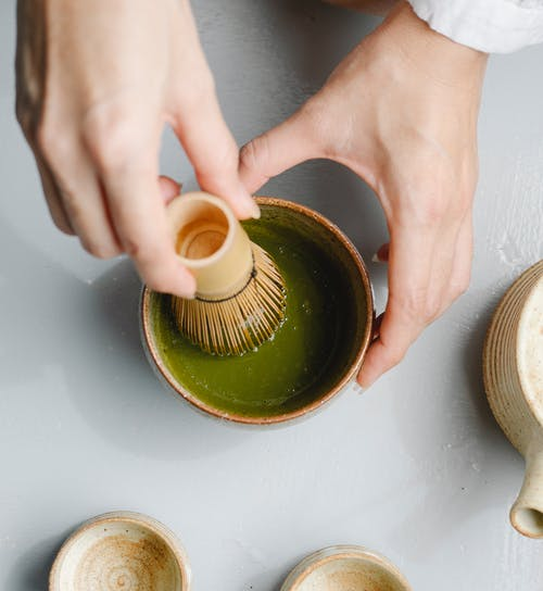 Top view of crop anonymous person using bamboo whisk while brewing hot matchaa tea ceremony