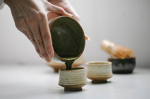 Close-Up Photo of Person Pouring Freshly Made Matcha Drink