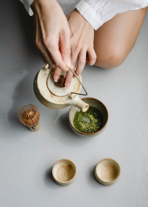 Woman pouring herbal tea from teapot for tea ceremony