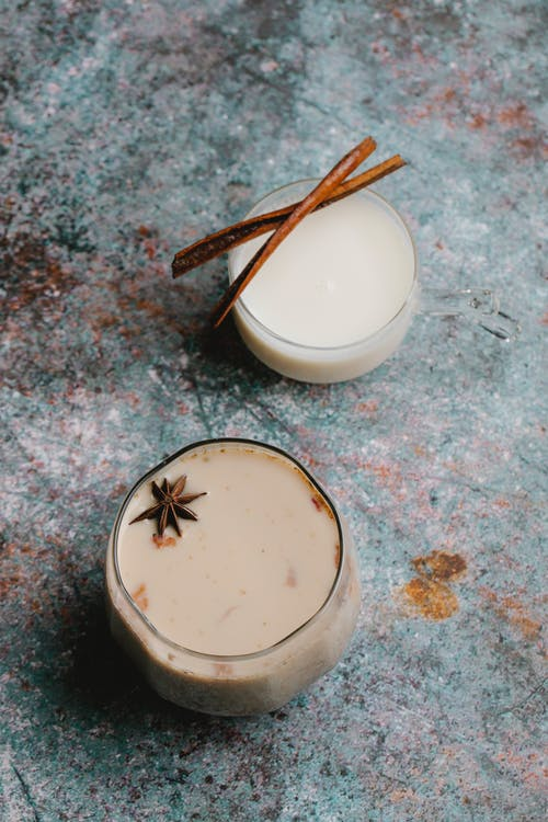 Top view of milky cocktails with spice decorated with anise star and cinnamon sticks served on table