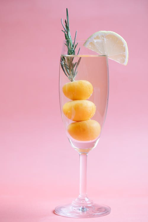 Crystal cocktail decorated with slice of fresh lemon and kumquat on pink background of studio