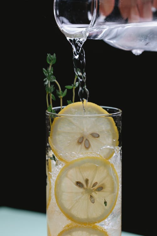Person pouring liquid from glass jug into glass with lemon