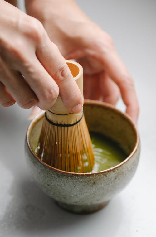 From above of crop anonymous person mixing matcha powder and water with bamboo whisk in ceramic bowl