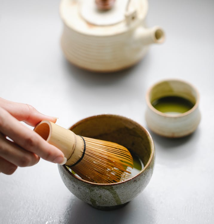 From above of crop anonymous female making matcha tea with bamboo whisk for tea ceremony near teapot on table