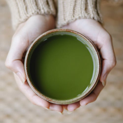 Top view of crop anonymous female showing bowl full of green tea of matcha in hands on blurred background