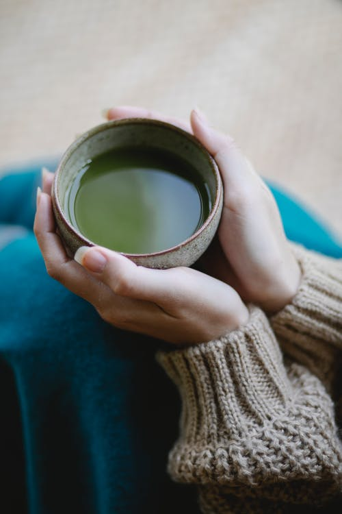 From above of crop anonymous female in knitwear sitting on floor with cup of matcha tea