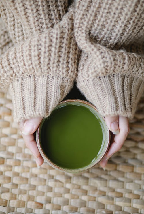 Top view of crop anonymous female in soft knitted clothes with hot matcha tea