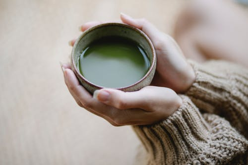 High angle of crop anonymous female in knitwear with ceramic cup of hot matcha tea