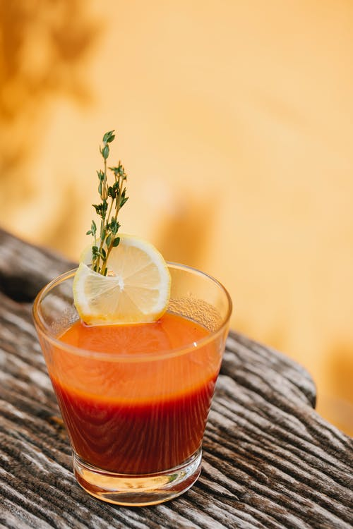 Transparent glass of Bloody Mary cocktail decorated with fresh lemon slice and thyme sprig on rough surface