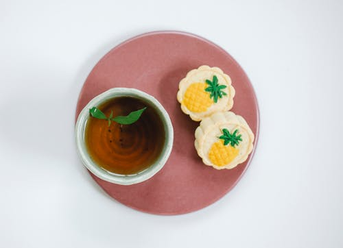 Top view of oriental cup of fresh tea with fresh mint leaves on plate with delicious pastries on light background
