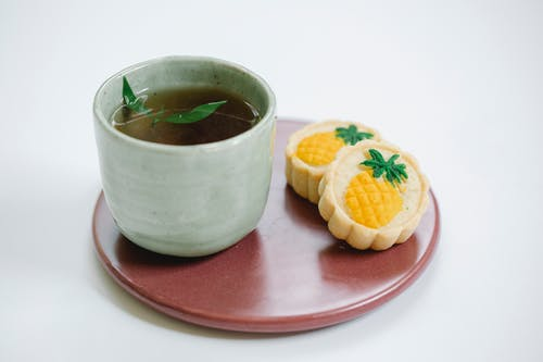 Black tea with tasty sweet pastries on plate
