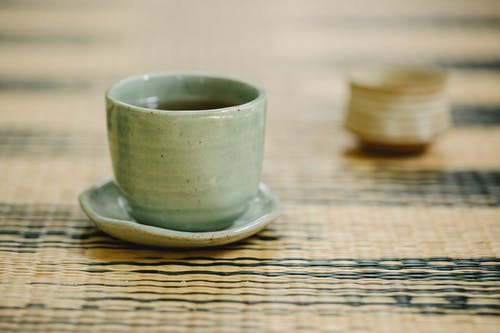 Round shaped oriental cups of hot fresh tea with saucer on ornamental mat in daytime