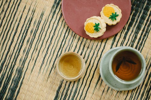 From above of oriental cups of green and black tea near plate with yummy crunchy treats on wicker mat