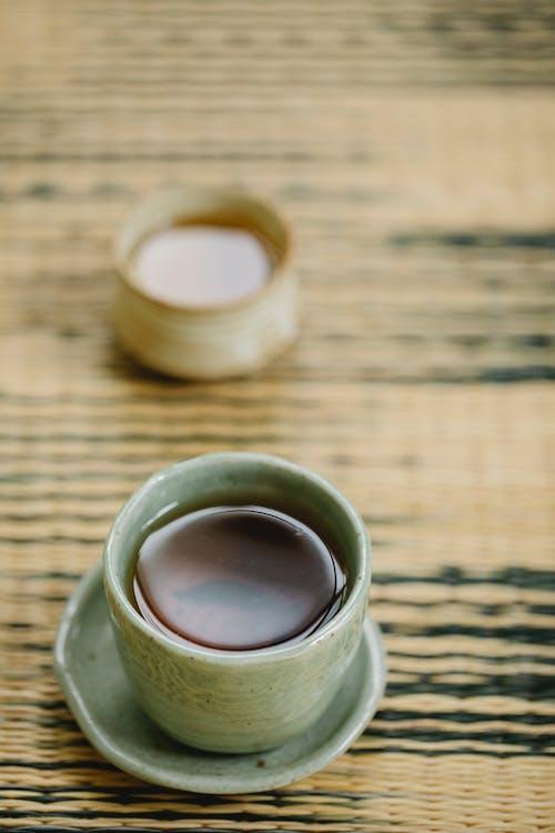 Ceramic cups of tea on straw mat