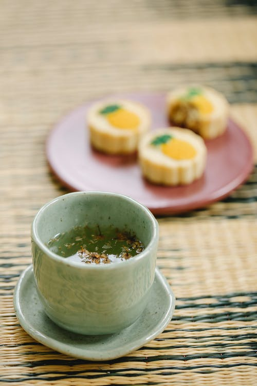 From above of ceramic cup of aromatic tea with herb leaves near plate with delicious pastries on wicker mat