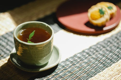 High angle of fresh black tea with green mint leaves in oriental cup with saucer on straw mat