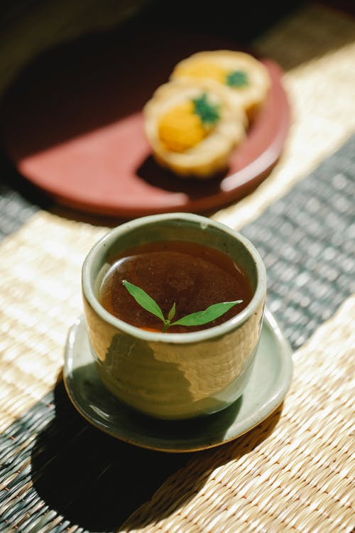 Cup of black tea with mint on straw mat