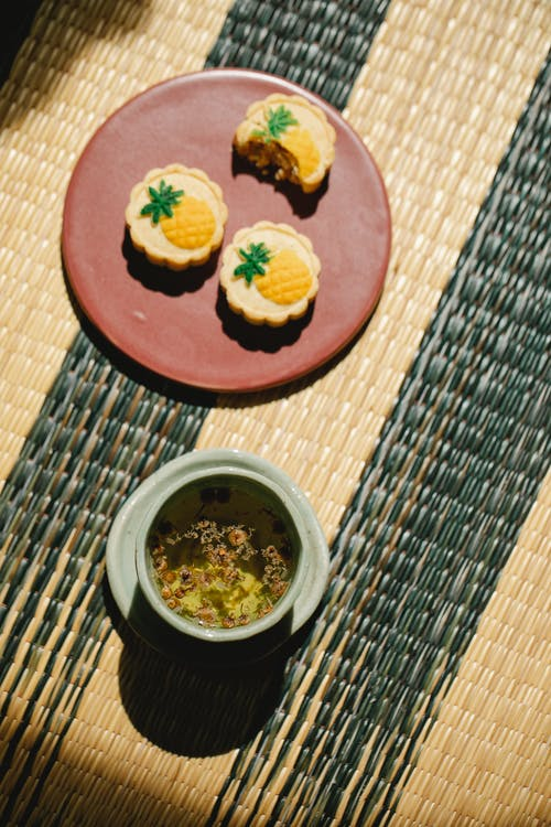 Top view of ceramic cup of green tea with aromatic leaves near plate with sweet treats on wicker mat