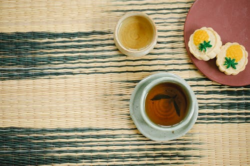 High angle of aromatic black and green tea in ceramic Asian cups near plate with delicious pastries on table