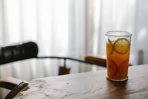 Glass of tasty lemonade on table in house