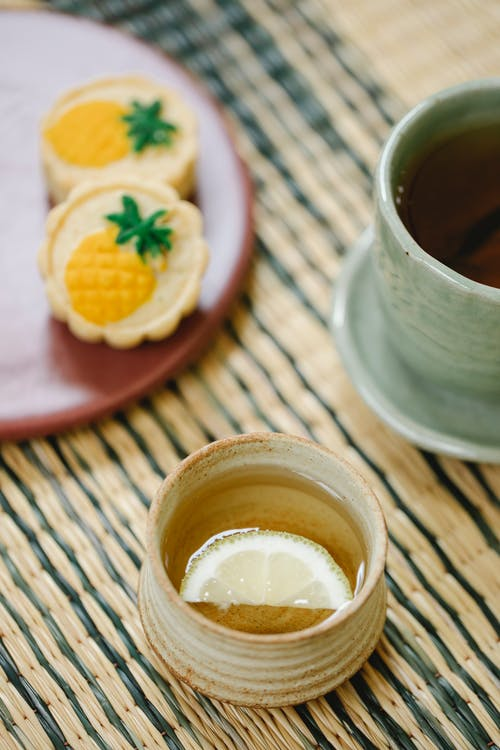 From above of cups of aromatic black and green tea with lemon slice near tasty crunchy pastries on straw mat
