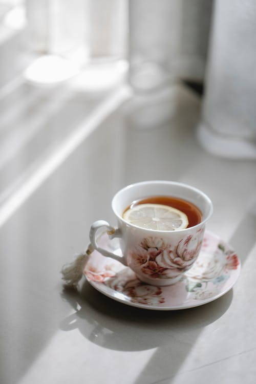 Ornamental porcelain cup of tea with lemon at home