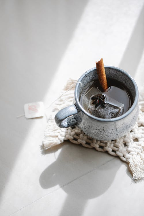 From above of ceramic cup with hot tea with cinnamon stick and anise on knitted napkin