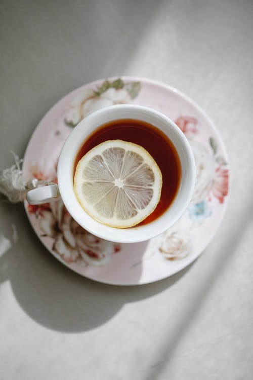 Top view of hot aromatic tea with slice of lemon in porcelain cup on saucer