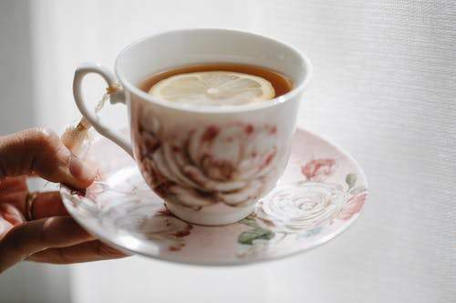 Hand of crop anonymous person holding elegant saucer with cup of hot aromatic tea with slice of lemon