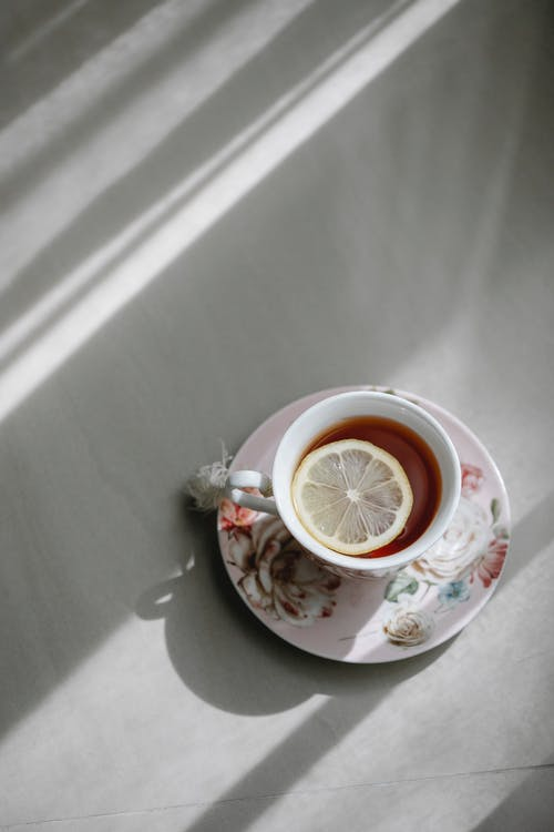 Top view of hot aromatic tea with slice of lemon on plate placed on table