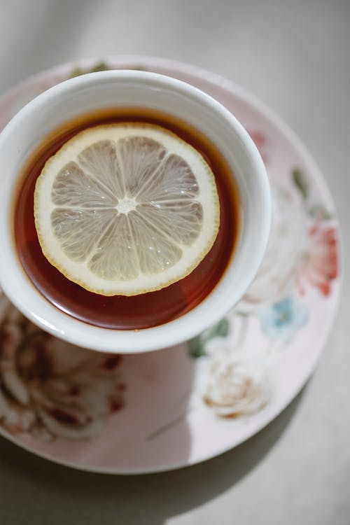 Closeup top view of hot fresh aromatic tea with lemon slice on saucer