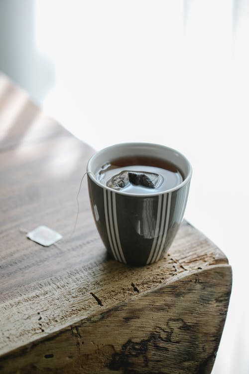 Ceramic mug with stripes of hot aromatic tea with teabag placed on wooden table