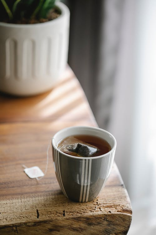 Ceramic mug with stripes of hot tasty tea with teabag placed on wooden table