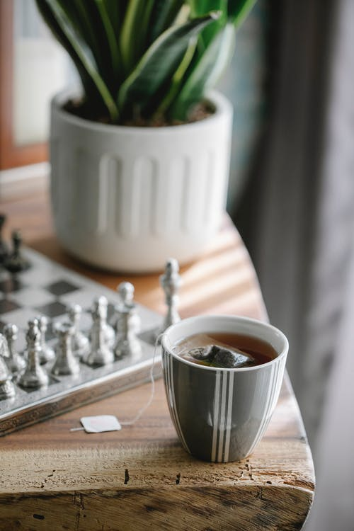 High angle of ceramic cup of hot aromatic tea with teabag on wooden table near chessboard
