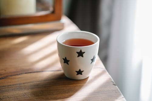 High angle of white ceramic cup with stars of hot tasty tea placed on wooden table