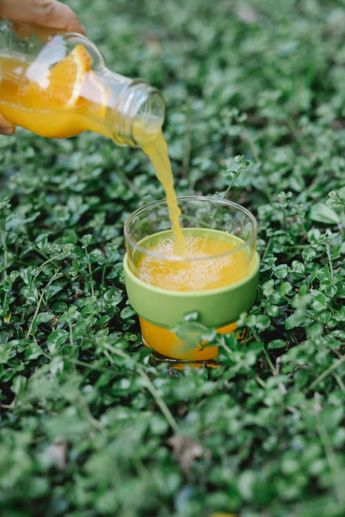 Crop person pouring orange juice