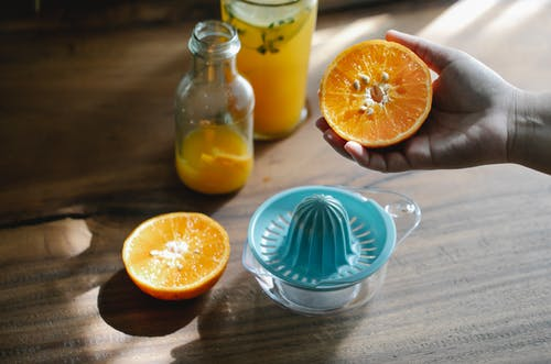 Crop anonymous person holding ripe citrus over wooden table with orange squeezer and glass bottle with fresh juice