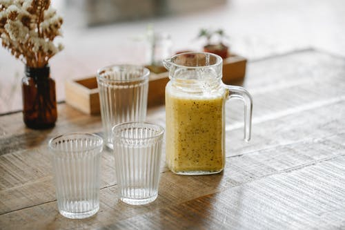 Jar with fresh tasty smoothie near empty glasses on wooden table in restaurant